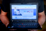 Image of someone holding a laptop featuring an online interface