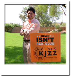 Photo of a proud KJZZ employee next to yard sign