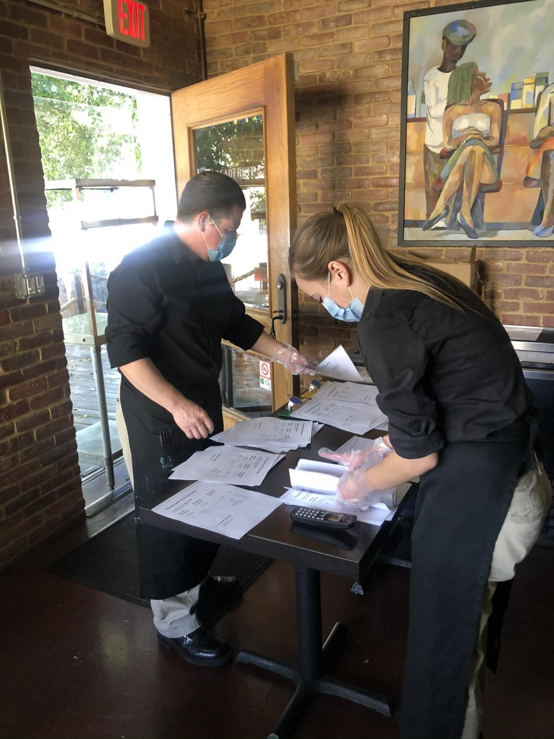 employees setting up table for takeout orders
