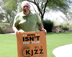 "KJZZ employee next to a ""News Isn't Red or Blue"" campaign sign"