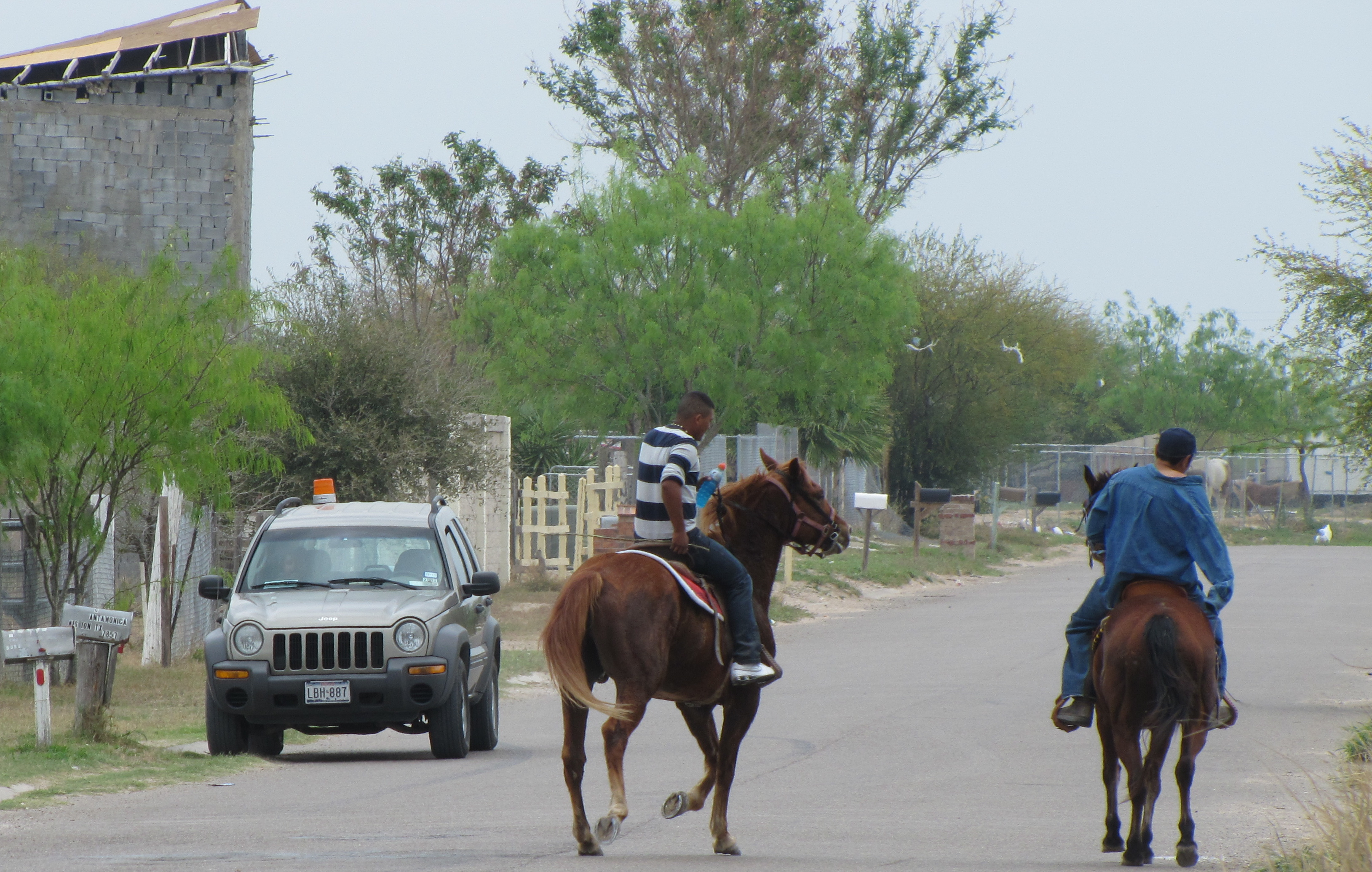 "Boys ride horses down a street in a ""colonia"" in Texas near the U.S.-Mexico border."