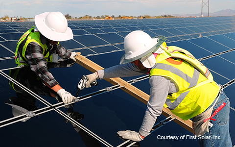 Workers install First Solar panels in Blythe, CA.