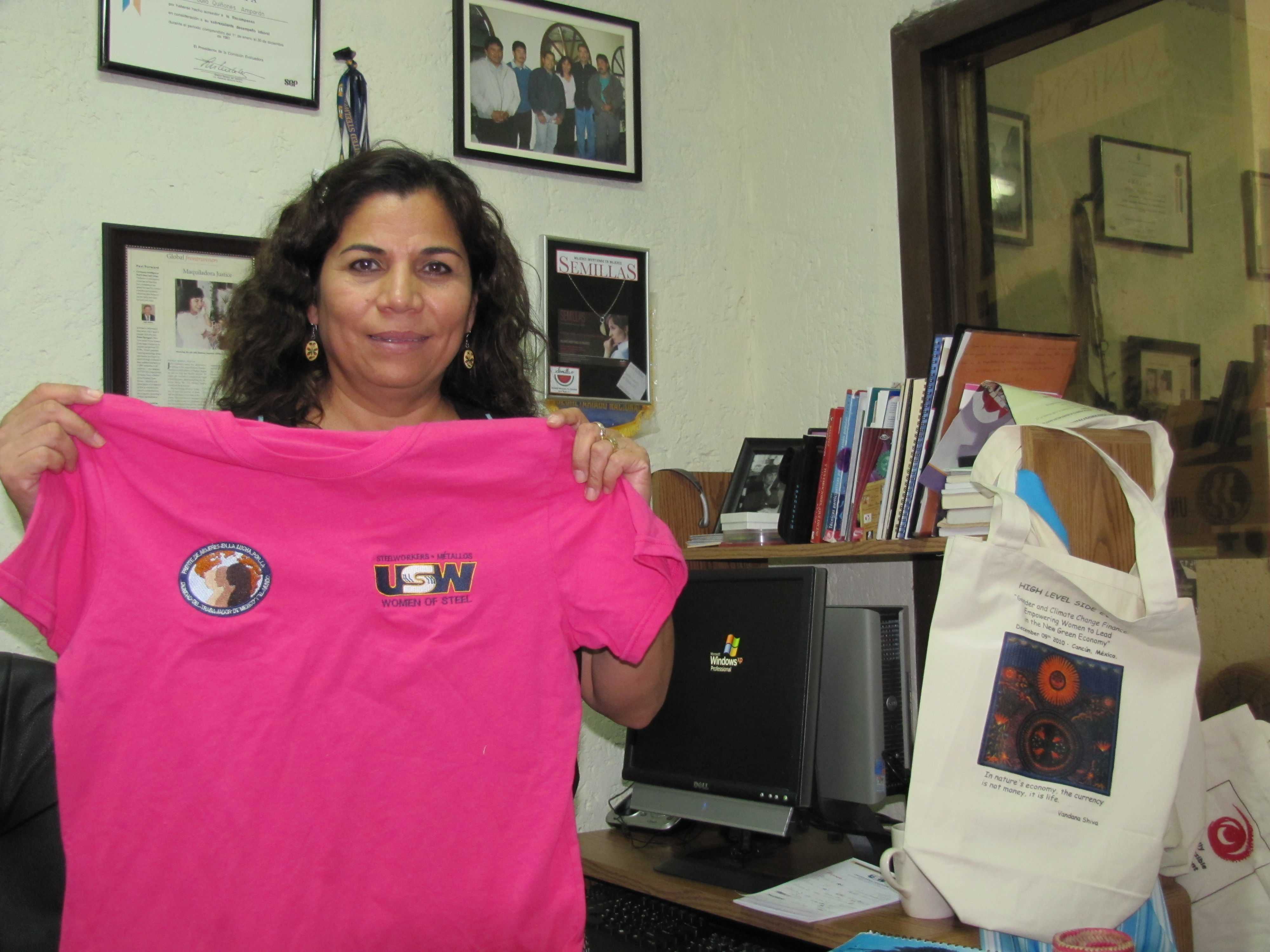 Julia Quinonez, president of the Border Committee of Women Workers in Piedras Negras, Mexico, shows a T-shirt the organization makes at its small textile shop.