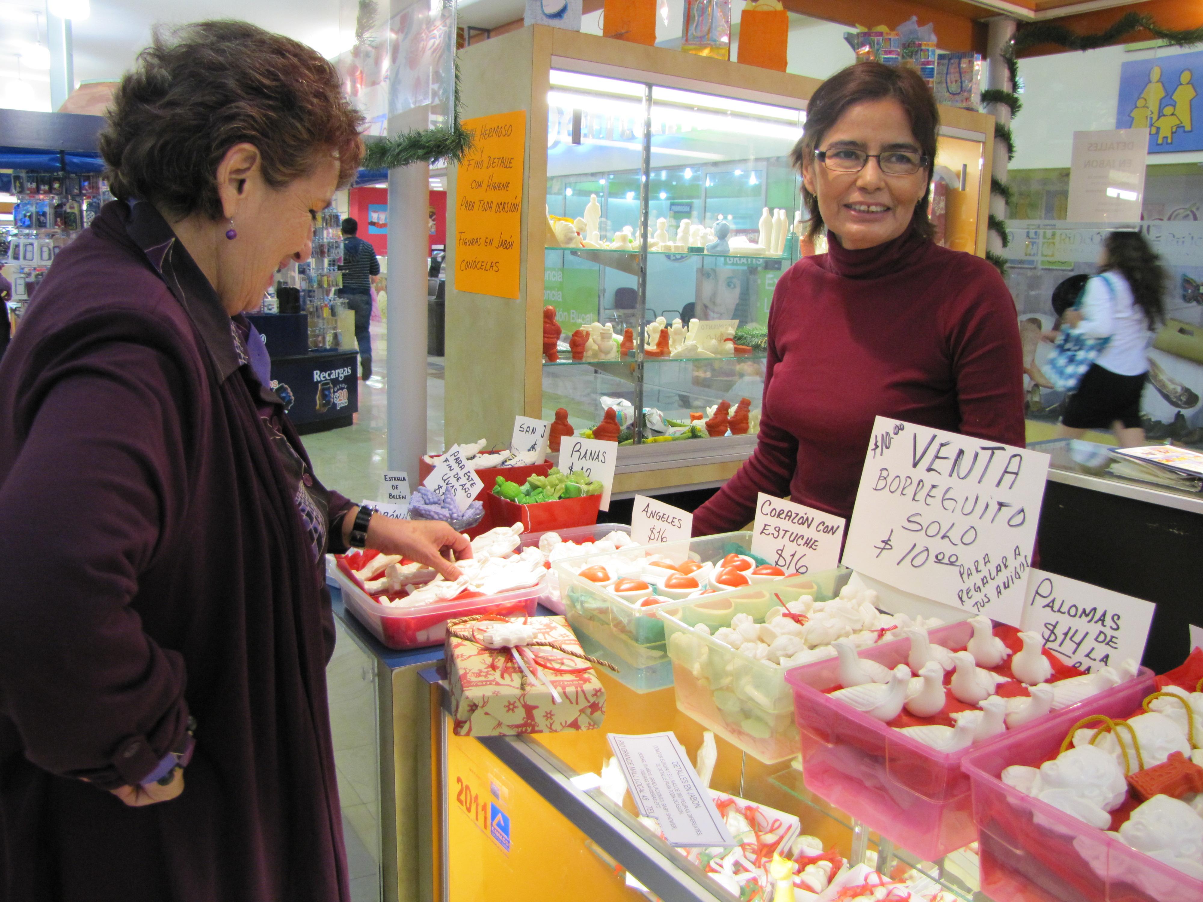 "Customer Rosa Maria Reynoso (left) shops for soaps at a mall in Ciudad Juárez during ""El Buen Fin"". Shop owner Ofelia Gomez (right) makes the soaps locally."