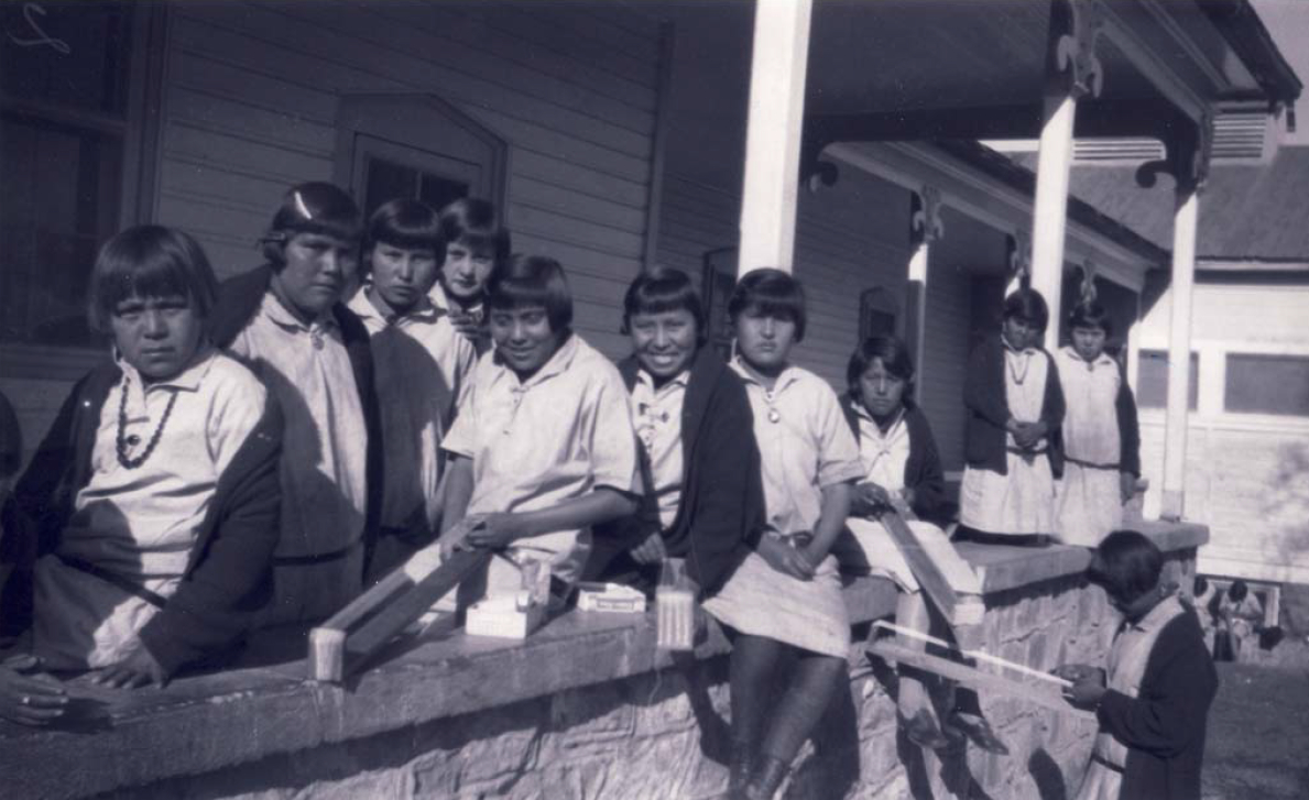 A photo of Dine' (Navajo) girls on the front porch of hospital/girls' dormitory at the Theodore Roosevelt School, taken sometime between 1928-29.