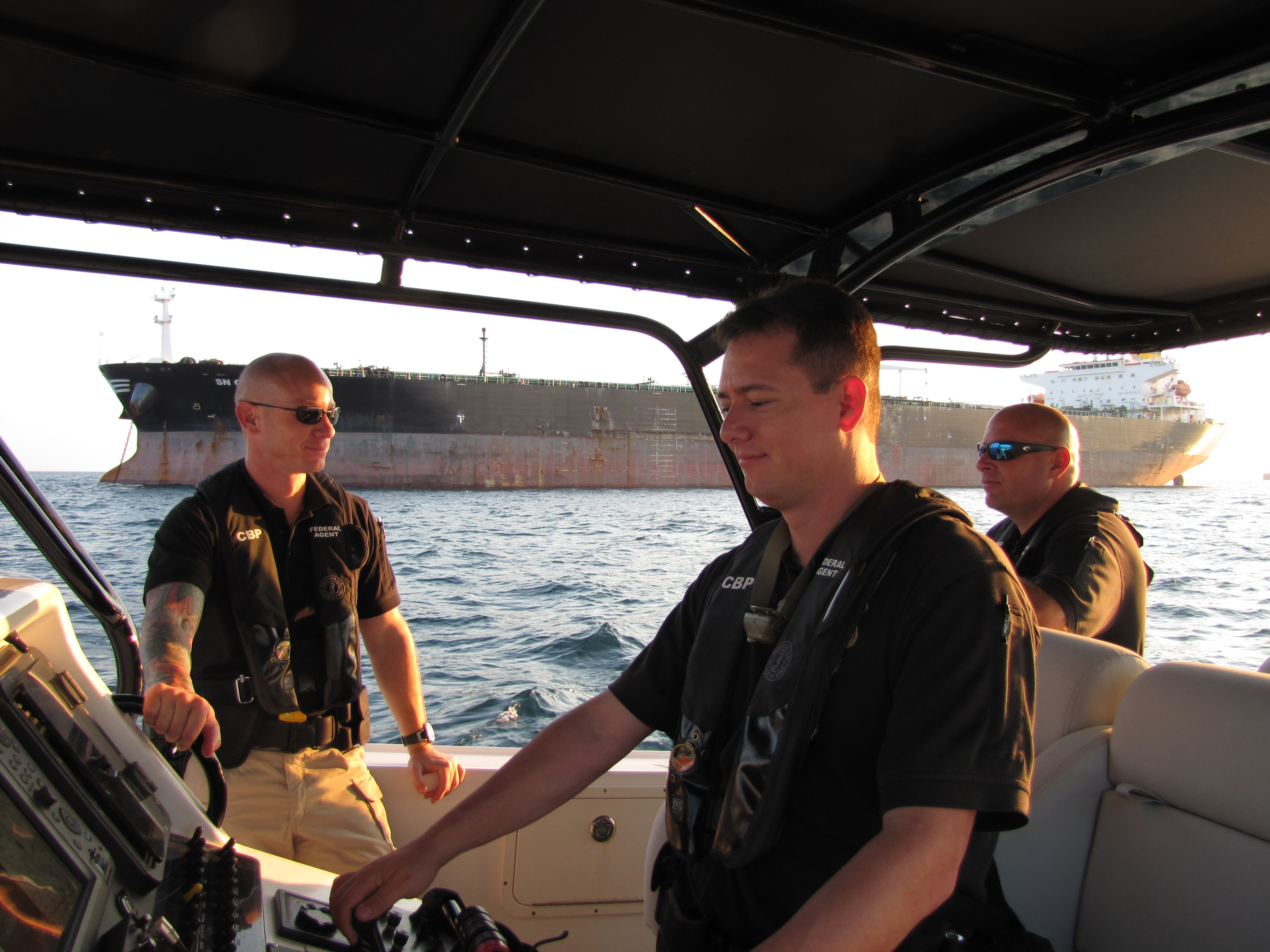 Homeland Security Marine Interdiction Agents on patrol. Behind them is an oil tanker in the Gulf of Mexico. The agents have the authority to inspect any watercraft they deem suspicious.