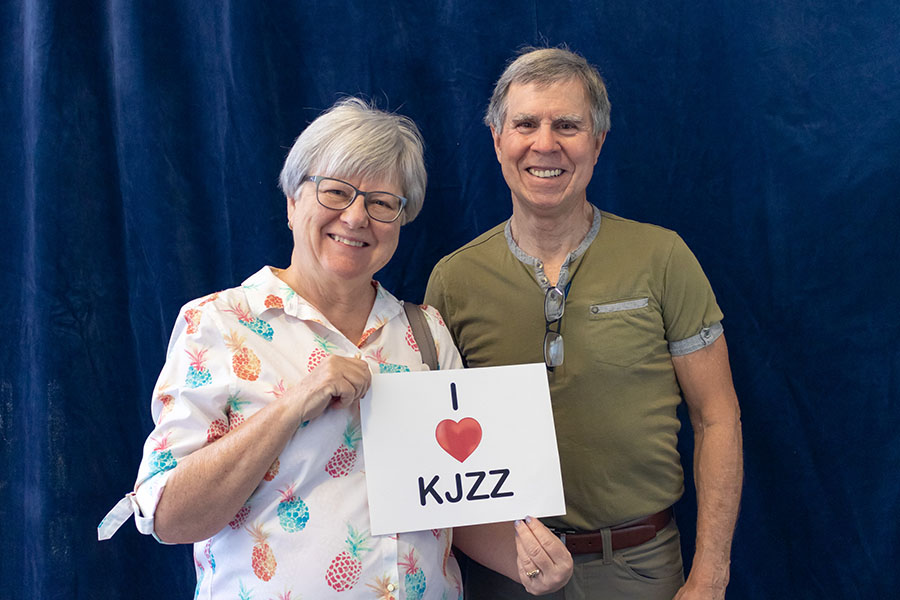 Two volunteers hold up a sign that says I Love KJZZ