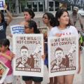"""Opponents of SB 1070 gathered outside of the federal courthouse in Phoenix on Tuesday with signs that read """"We wil not comply,"""" and """"Down with SB 1070"""" in Spanish."""