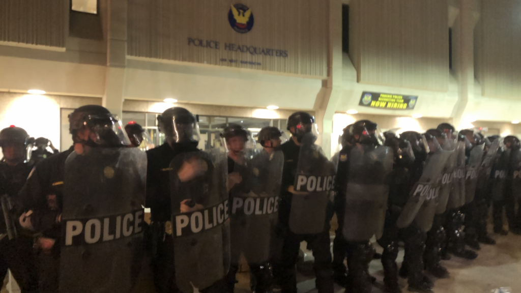 Phoenix Police officers in riot gear outside their headquarters during a protest.