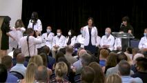 woman wearing white doctor coat smiles at camera