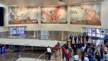 photo taken from escalator showing three panels of mural