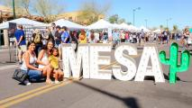 people posing by large letters that read Mesa