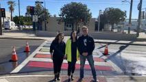3 people standing next to rainbow crosswalk