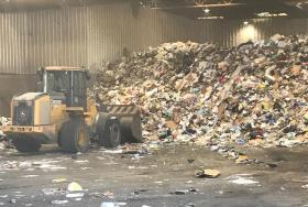 Tractors bail trash to be sorted into bales