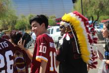 Washington Redskins fans walk past protesters as they head into the Cardinals game on Sunday.