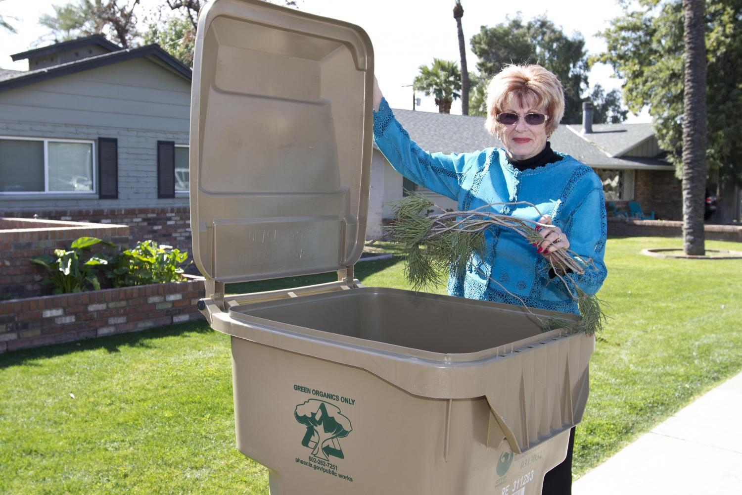 woman standing next to recycle bin