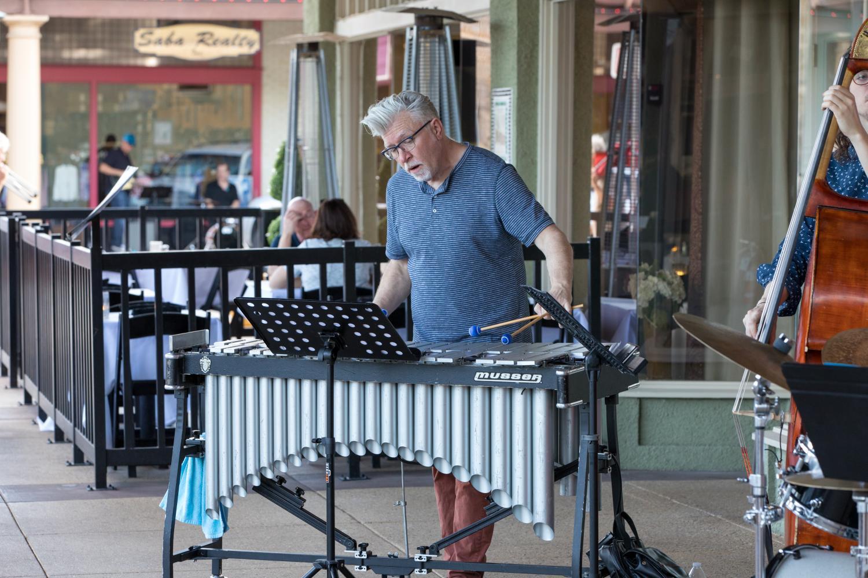 musician on sidewalk outside business