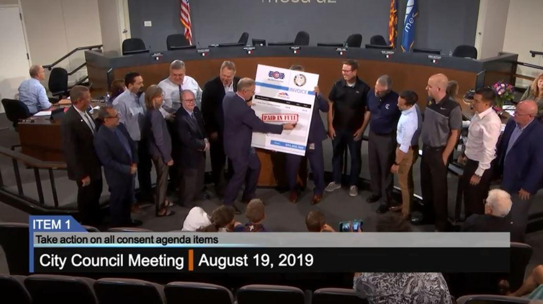 Mesa Mayor John Giles signs an oversized invoice at the August 19, 2019 city council meeting