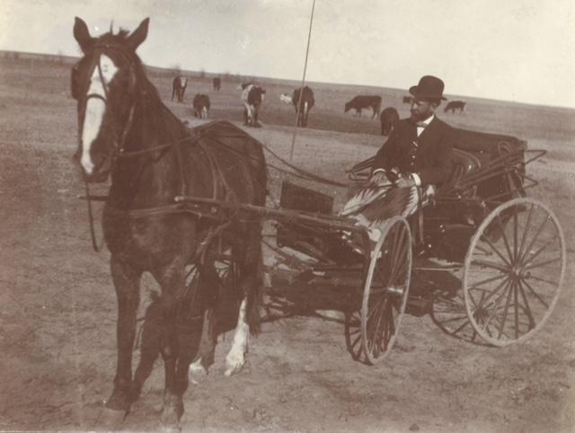 Black-and-white photo of CJ Babbitt on a cart with a horse