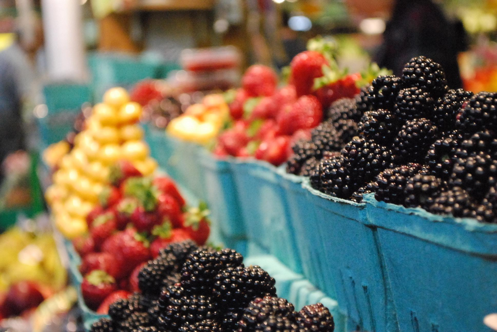 Blackberries, strawberries and other cartons of produce sit in a row