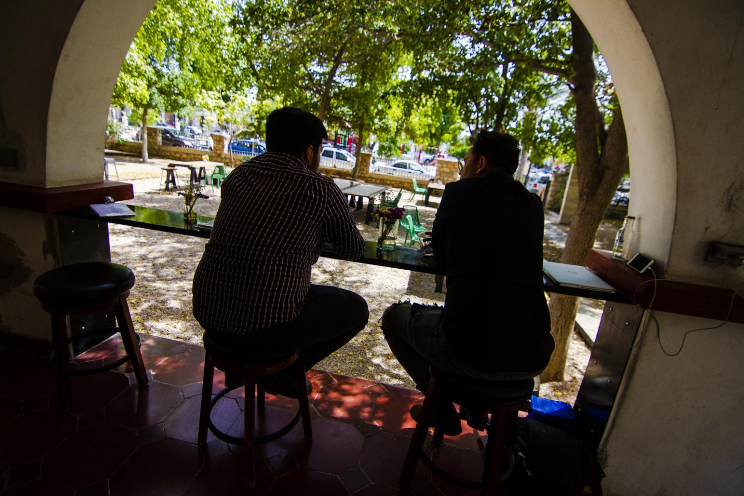 Two young freelance graphic designers chat at Cafe Central