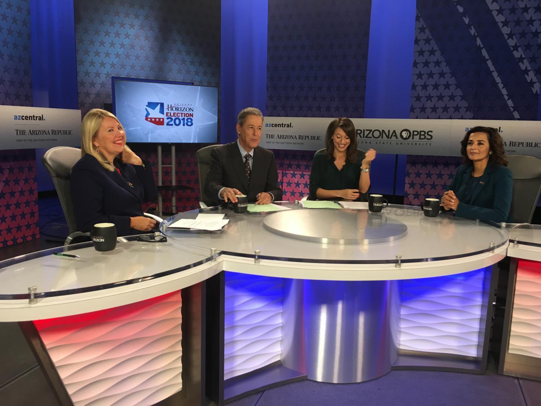 Debbie Lesko and Hiral Tipirneni sit behind a desk with moderators at Arizona PBS