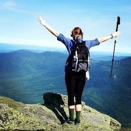 Caitlin Stewart raises her hands over a cliff
