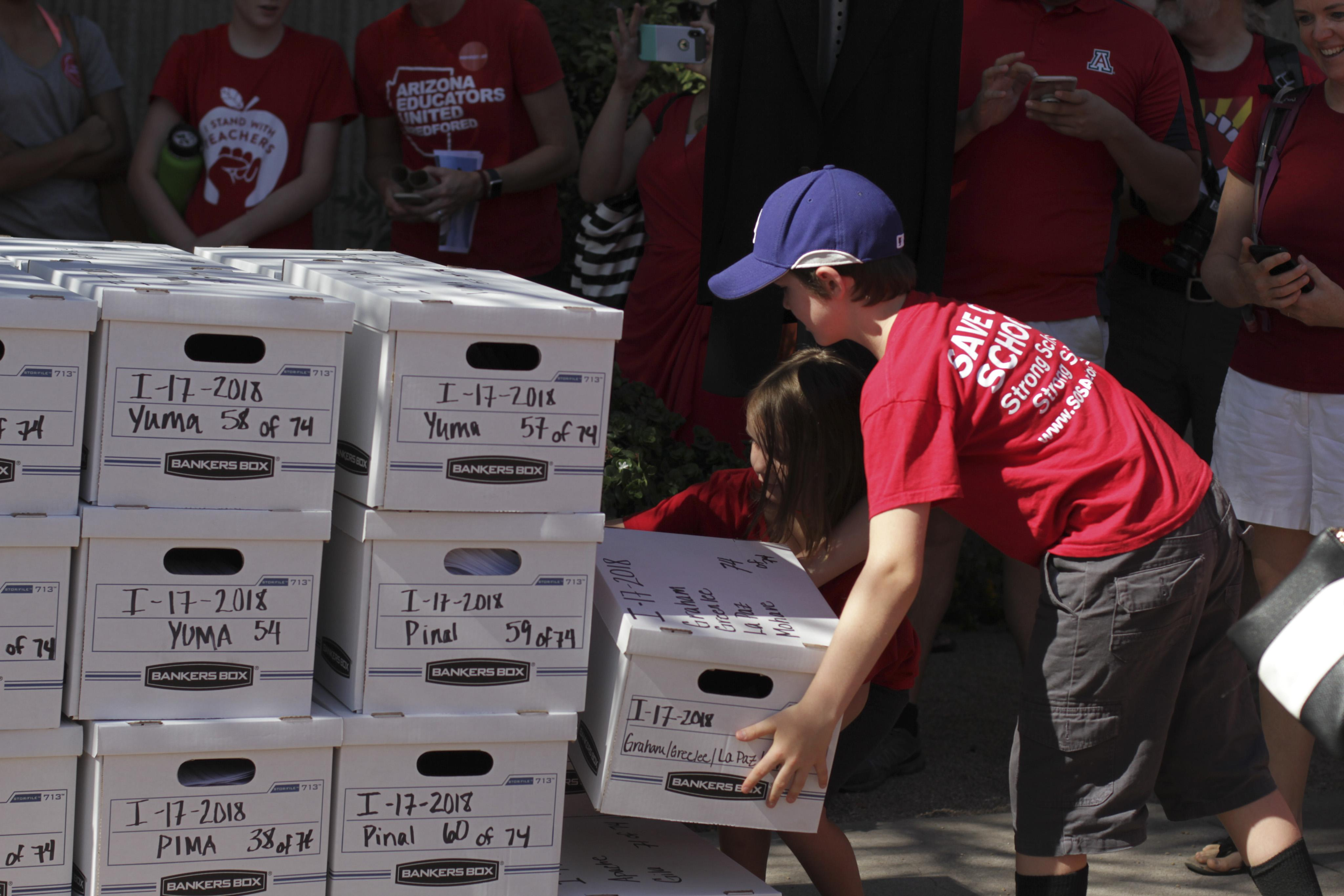 Kids stack up boxes of signatures supporting Invest in Education