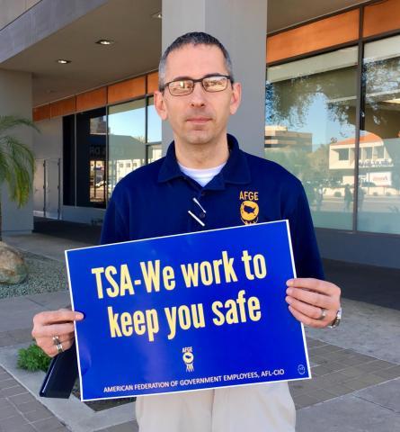 TSA employee holding protest sign on street corner