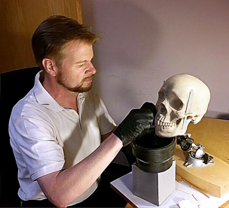 man working on skull model