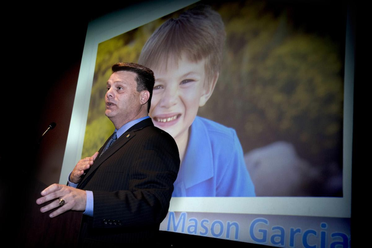 Marc Garcia, president & CEO of Visit Mesa, stands in front of a photo of his son, Mason Garcia, who has autism.