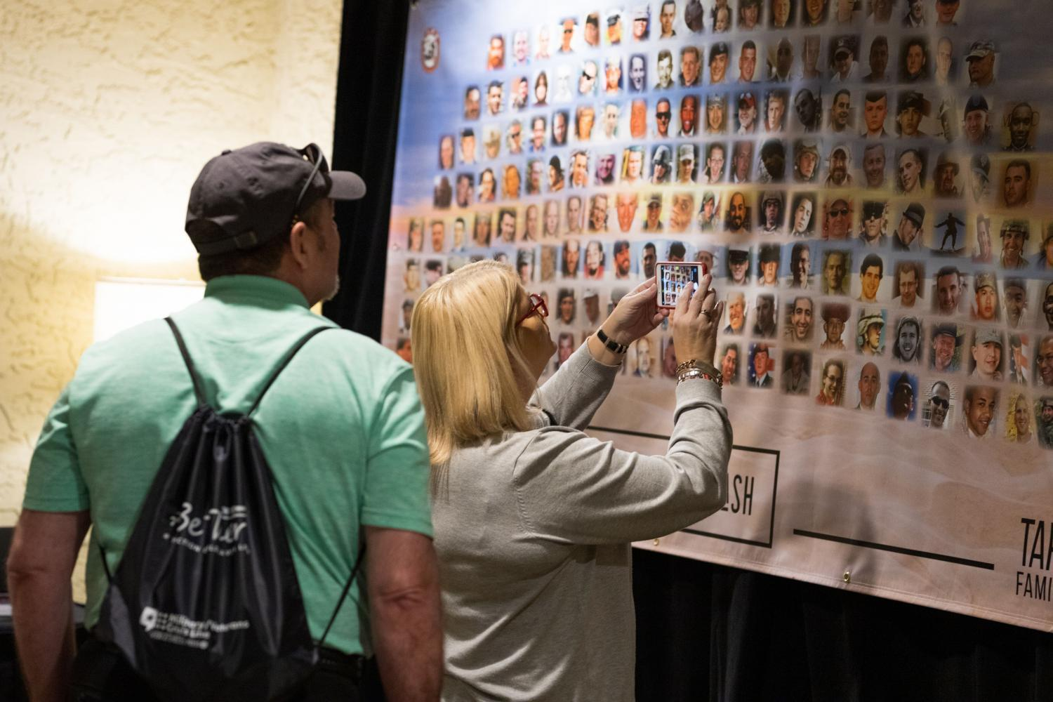 Military suicide survivors look at a photo montage of relatives who died of suicide.