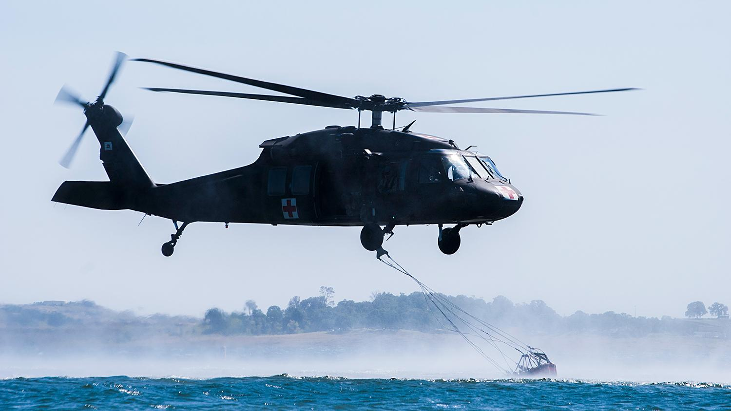 Blackhawk helicopter scoops up water in a bucket