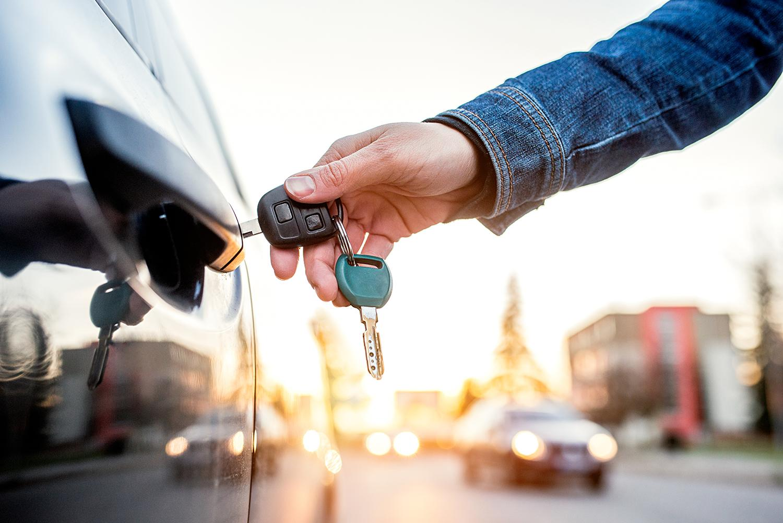 Hand with keys unlocking car