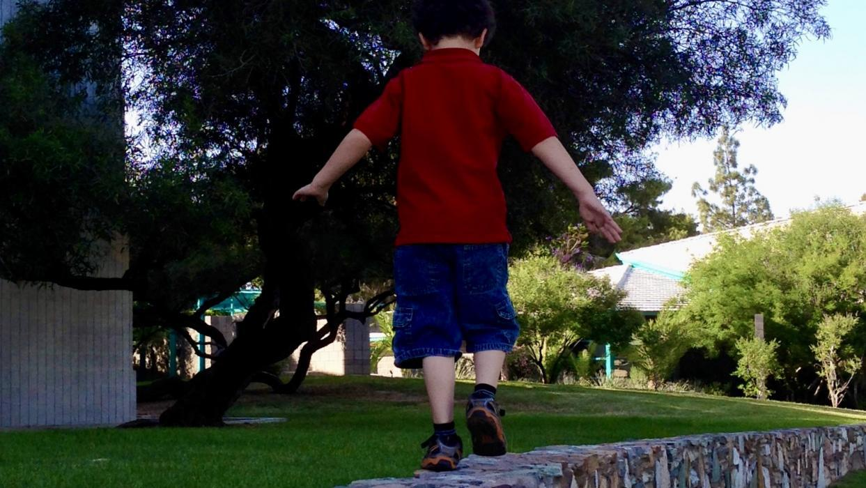 child walking on a wall
