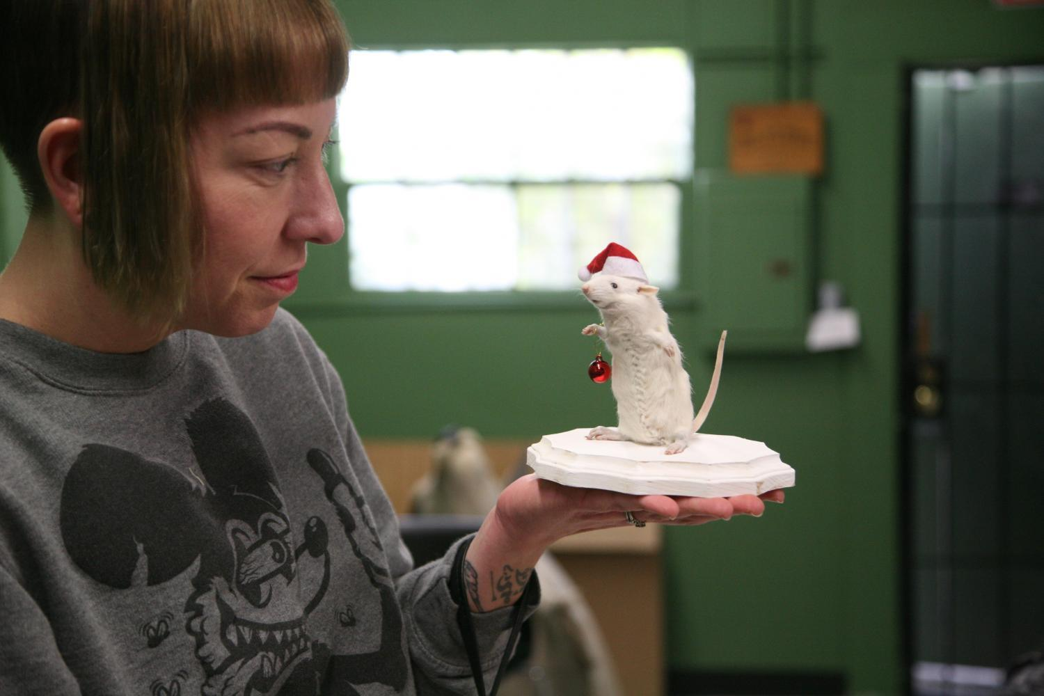 Courtney Perez holds a holiday stuffed rat