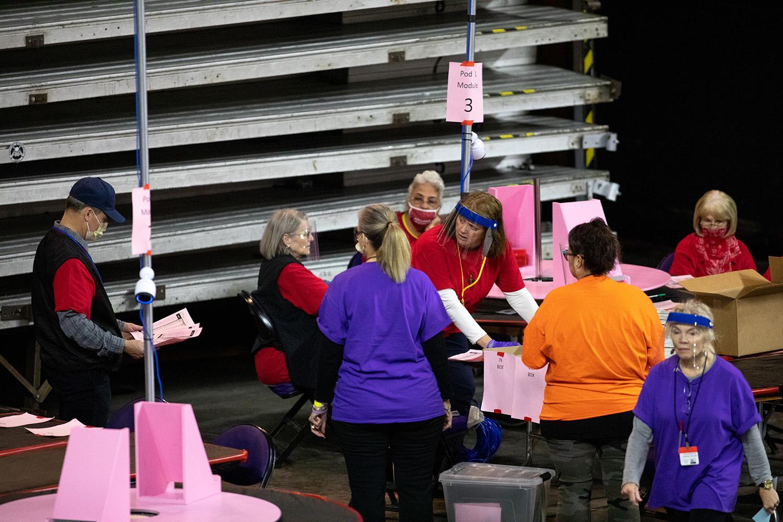 Contractors working for Cyber Ninjas examine and recount ballots