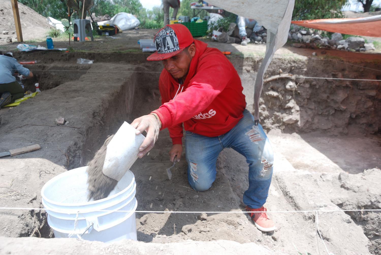 Adrian Aleman Martinez uses a trowel to scrape dirt into a bucket.