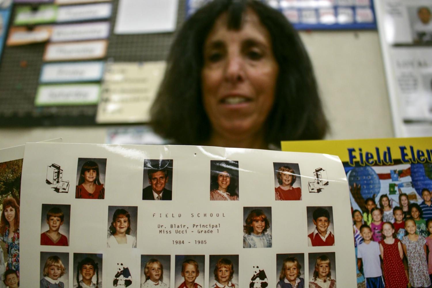 Ms. Ucci holds up a class picture from her first class at Field Elementary in 1984