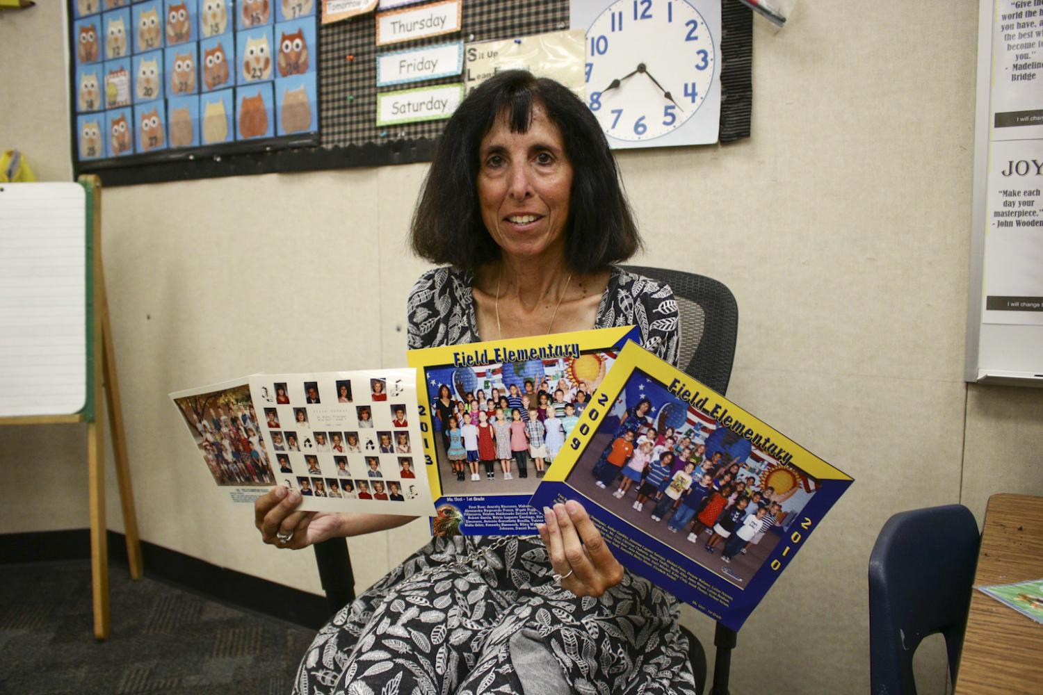 Ms. Ucci holds up class pictures from previous years