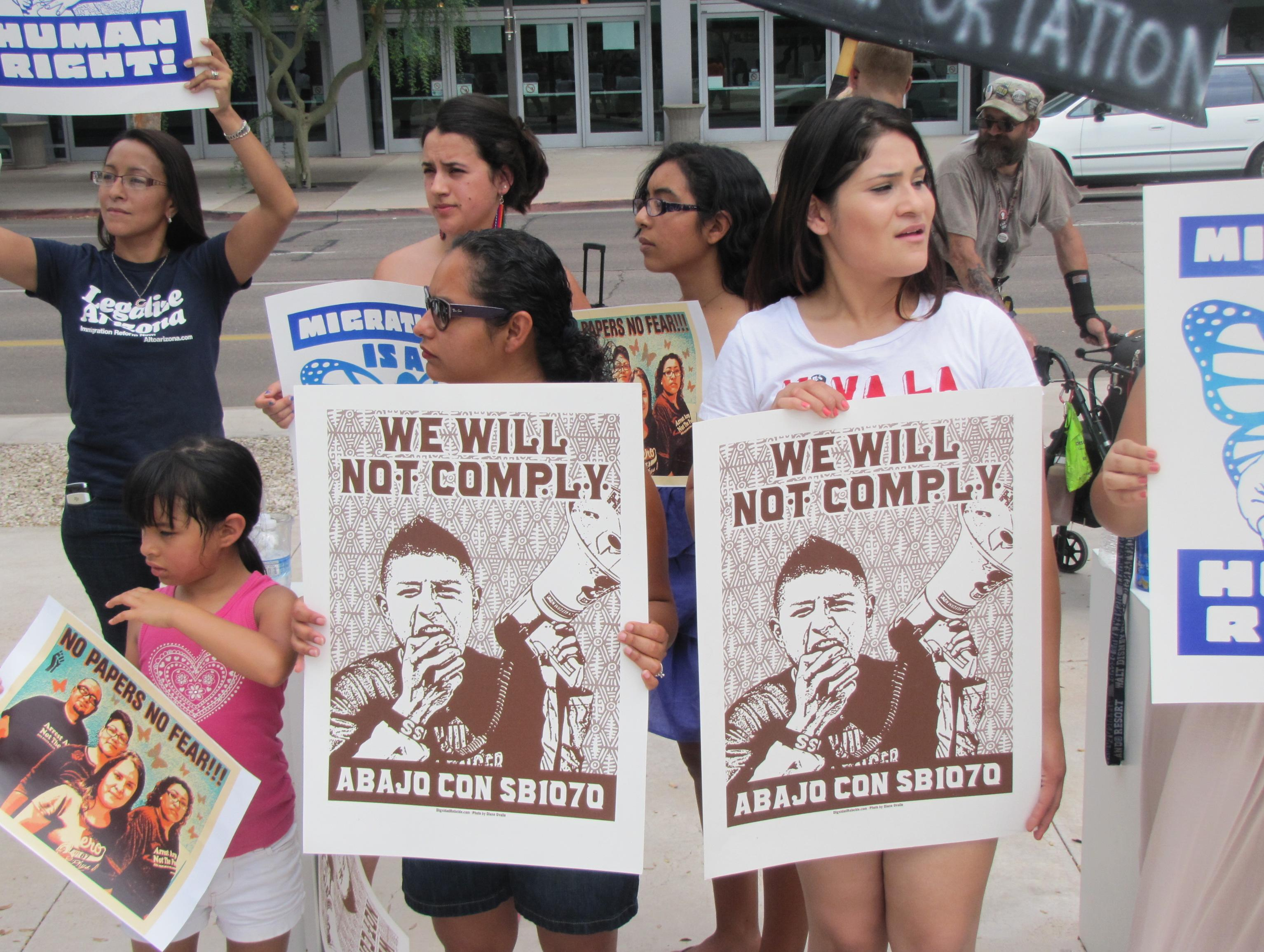 "Opponents of SB 1070 gathered outside of the federal courthouse in Phoenix on Tuesday with signs that read ""We wil not comply,"" and ""Down with SB 1070"" in Spanish."