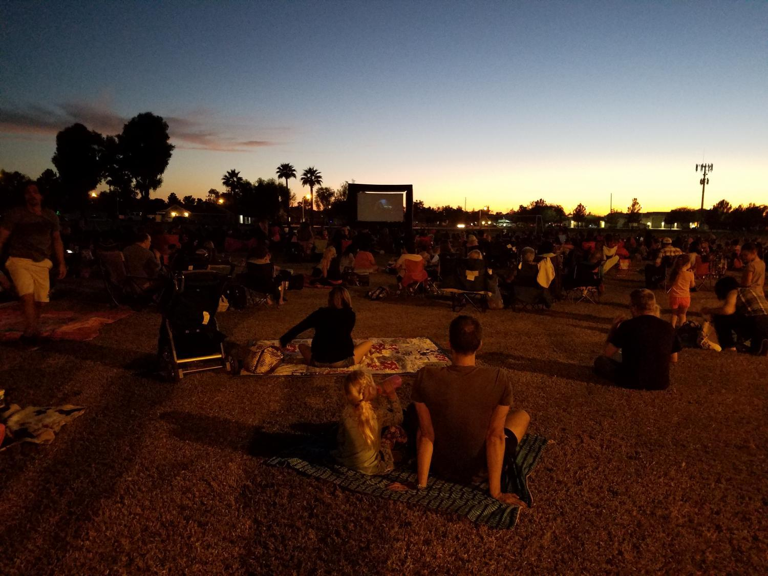 people enjoy a movie at a park