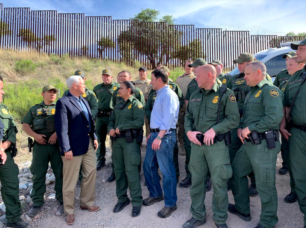 Flanked by a group of olive-uniformed Border Patrol agents and with the border fence topped in concertina wire as the backdrop, Pence called on Congress to harden immigration rules against asylum seekers.