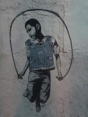 A mural of a boy donning a bullet-proof vest to jump rope on a street in Nogales, Sonora, across the street from Nogales, Arizona