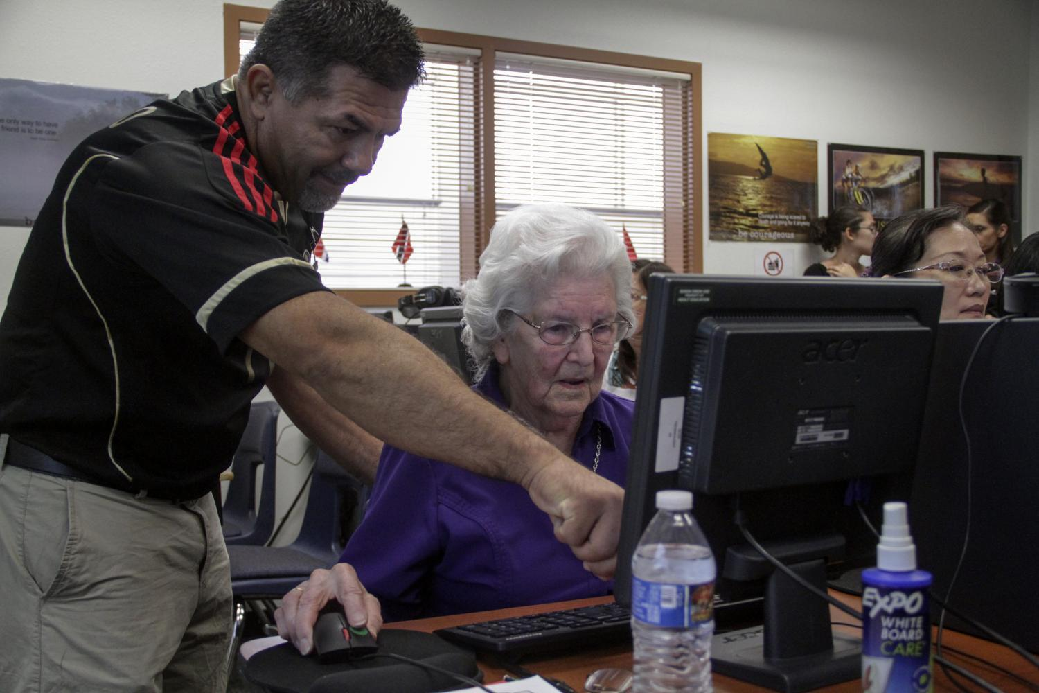 Mauricio Ramirez shows Frances Smith how to use the computer in a Queen Creek adult education class