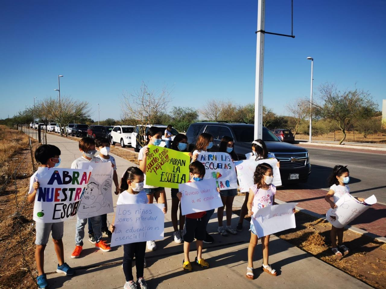 children hold up signs during protest