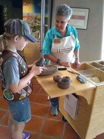 Volunteer Twig Johnson discussing prehistoric artifacts with a girl scout visitor