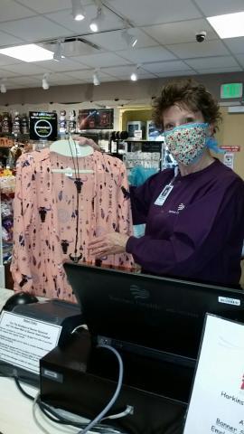 woman wearing mask holding up shirt