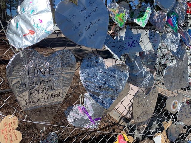 Foil hearts on fence after hate crime.