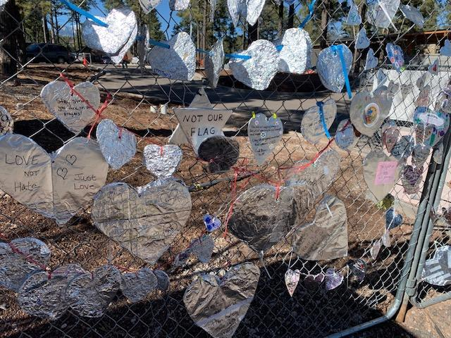 Foil hearts on fence after hate crime.